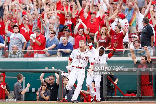 Todd Frazier and Brandon Phillips of the Cincinnati Reds celebrate after Ryan Ludwick hit the gamewinning home run in the tenth inning against the St...