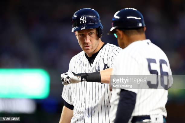 Todd Frazier fist bumps first base coach Tony Pena of the New York Yankees after hitting a single in the fifth inning during the game against the...