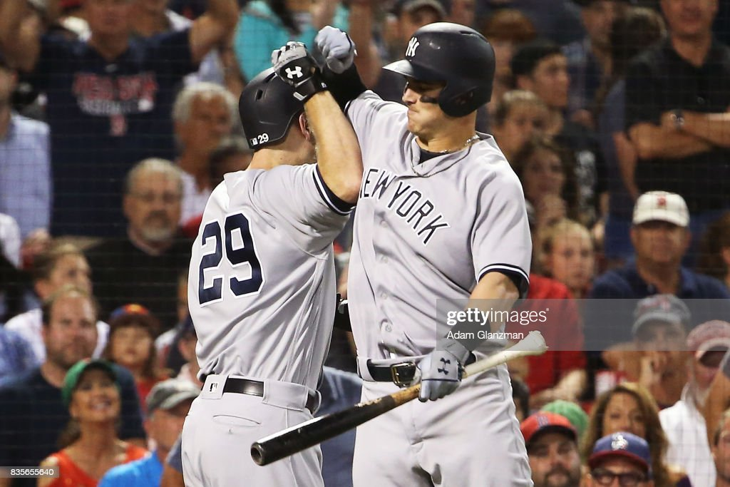 Todd Frazier #29 high fives Tyler Austin #26 of the New York Yankees after hitting a solo home run in the sixth inning of a game aggainst the Boston Red Sox at Fenway Park on August 19, 2017 in Boston, Massachusetts.