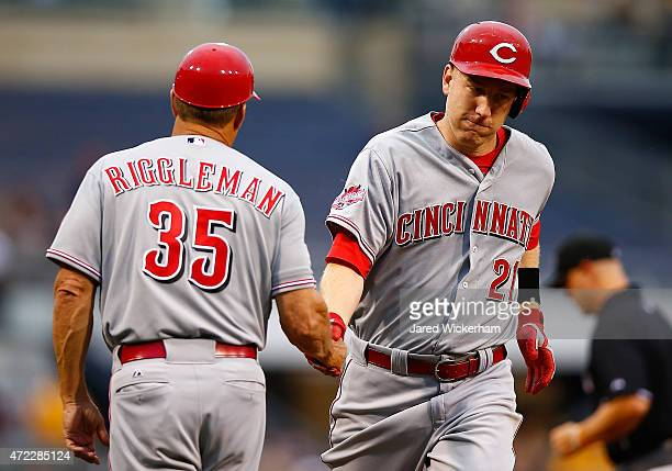 Todd Frazier of the Cincinnati Reds is congratulated by third base coach Jim Riggleman following a solo home run in the second inning against the...