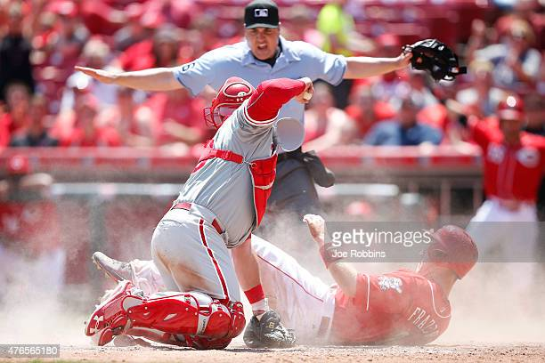 Todd Frazier of the Cincinnati Reds slides home with a run in the seventh inning ahead of the tag by Cameron Rupp of the Philadelphia Phillies during...