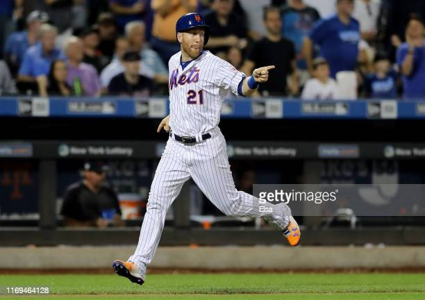 Todd Frazier of the New York Mets points to teammate Juan Lagares as he stands on second base in the fifth inning at Citi Field on August 21 2019 in...