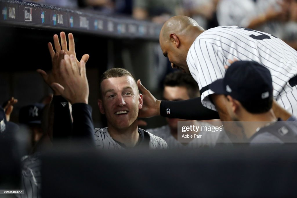 Todd Frazier #29 of the New York Yankees celebrates with his teammates after sliding save to home plate to score on Brett Gardner #11 sacrifice fly to center field against the Cleveland Indians during the fifth inning in Game Four of the American League Divisional Series at Yankee Stadium on October 9, 2017 in the Bronx borough of New York City.