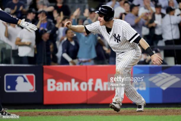 Todd Frazier of the New York Yankees celebrates with his teammates after sliding save to home plate to score on Brett Gardner sacrifice fly to center...