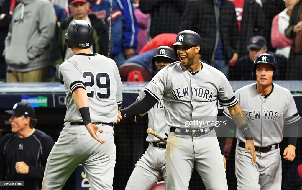 Todd Frazier #29 of the New York Yankees celebrates with teammates as he returns to the dugout after scoring on a single by Brett Gardner #11 in the ninth inning against the Cleveland Indians in Game Five of the American League Divisional Series at Progressive Field on October 11, 2017 in Cleveland, Ohio.