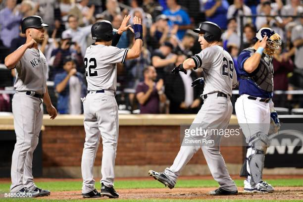 Todd Frazier of the New York Yankees is congratulated by his teammates after hitting a three run home run during the fourth inning against the Tampa...