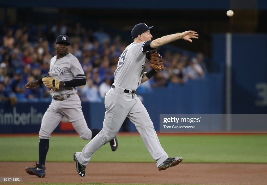 Todd Frazier #29 of the New York Yankees makes a toss to second base that was mishandled by Starlin Castro #14 leading to an unearned run in the first inning during MLB game action against the Toronto Blue Jays at Rogers Centre on September 22, 2017 in Toronto, Canada.
