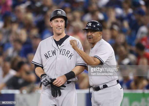 Todd Frazier of the New York Yankees shares a smile with first base coach Tony Pena after being hit by pitch in the ninth inning during MLB game...