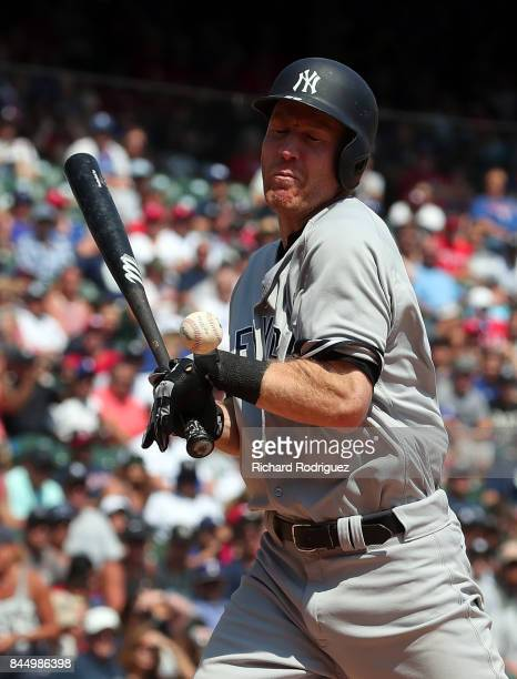Todd Frazier of the New York Yankees winces after being hit by a pitch from Andrew Cashner of the Texas Rangers in the 8th inning of a game at Globe...