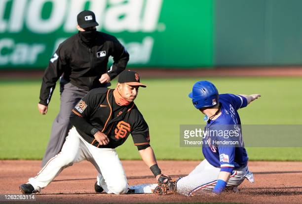 Todd Frazier of the Texas Rangers steals second base sliding in ahead of the tag of Donovan Solano of the San Francisco Giants in the top of the...