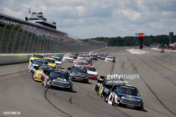 Todd Gilliland, driver of the Mobil 1 Toyota, and Kyle Busch, driver of the Cessna Toyota, lead the field into turn one during the NASCAR Camping...