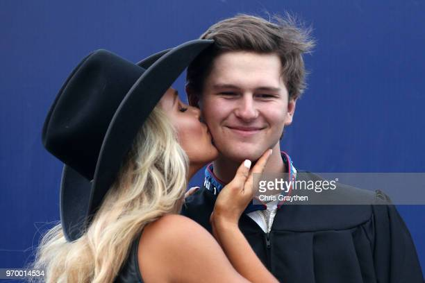 Todd Gilliland driver of the Mobil 1 Toyota gets a kiss from the Great American Sweethearts as he receives his high school diploma prior to the...