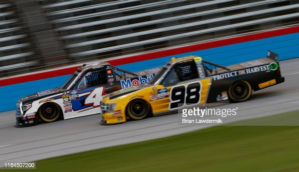 Todd Gilliland driver of the Mobil 1 Toyota races Grant Enfinger driver of the ProtectTheHarvestcom Ford during the NASCAR Gander Outdoors Truck...