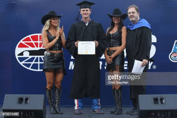Todd Gilliland driver of the Mobil 1 Toyota stands on stage as he receives his high school diploma prior to the NASCAR Camping World Truck Series PPG...