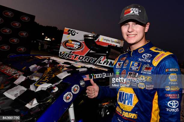 Todd Gilliland driver of the NAPA Auto Parts Toyota gives a thumbs up after placing the KN winner's sticker on his car in victory lane after winning...