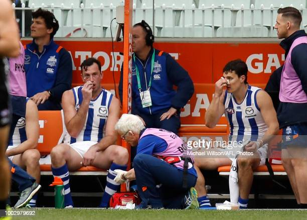 Todd Goldstein of the Kangaroos and Scott Thompson of the Kangaroos are treated after leaving the field with the blood rule during the 2018 AFL round...