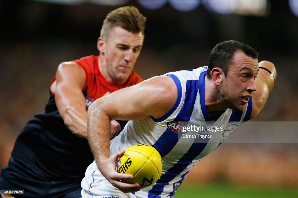 Todd Goldstein of the Kangaroos evades Lynden Dunn of the Demons during the round 14 AFL match between the Melbourne Demons and the North Melbourne Kangaroos at Melbourne Cricket Ground on June 22, 2014 in Melbourne, Australia.