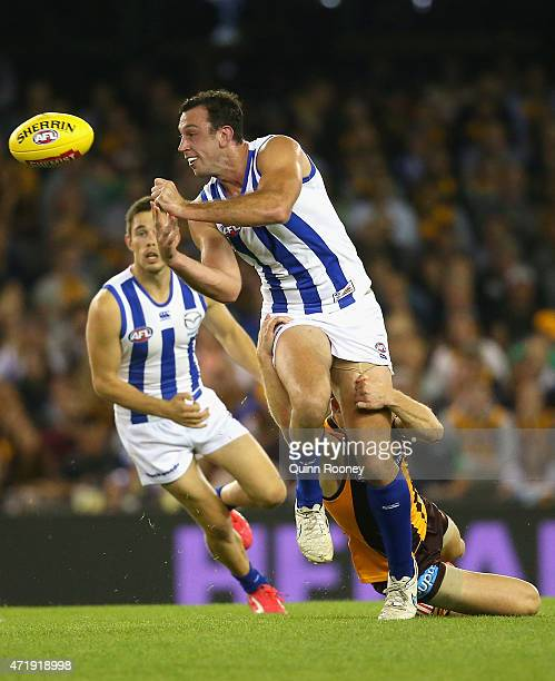 Todd Goldstein of the Kangaroos handballs whilst being tackled by Liam Shiels of the Hawks during the round five AFL match between the North...