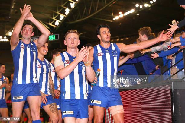 Todd Goldstein of the Kangaroos Jack Ziebell of the Kangaroos and Robbie Tarrant of the Kangaroos greet supporters after the Kangaroos victory during...