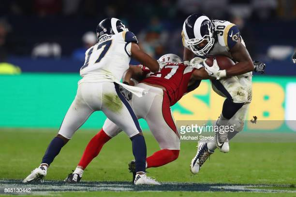 Todd Gurley II of Los Angeles Rams is tackled by Tyvon Branch of Arizona Cardinals during the NFL game between Arizona Cardinals and Los Angeles Rams...