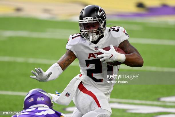 Todd Gurley of the Atlanta Falcons runs with the ball while being tackled by Cameron Dantzler of the Minnesota Vikings at U.S. Bank Stadium on...