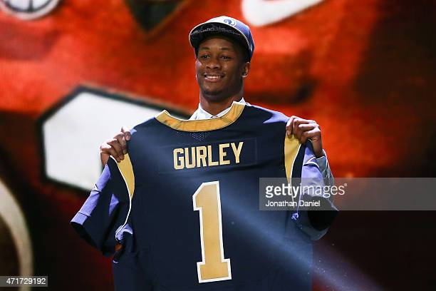 Todd Gurley of the Georgia Bulldogs holds up a jersey after being picked overall by the St Louis Rams during the first round of the 2015 NFL Draft at...