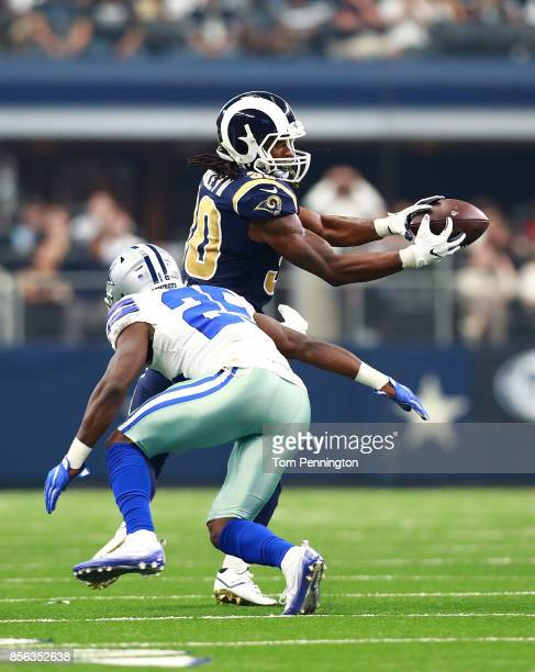 Todd Gurley of the Los Angeles Rams catches a pass as Xavier Woods of the Dallas Cowboys goes for the tackle in the first half of a game at AT&T...