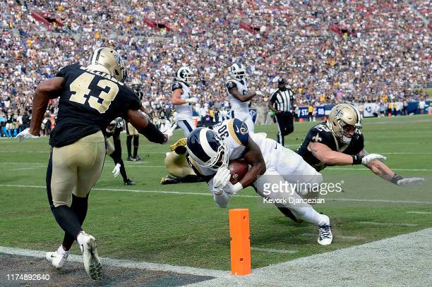 Todd Gurley of the Los Angeles Rams dives past A.J. Klein and Marcus Williams of the New Orleans Saints for a third quarter rushing touchdown at Los...