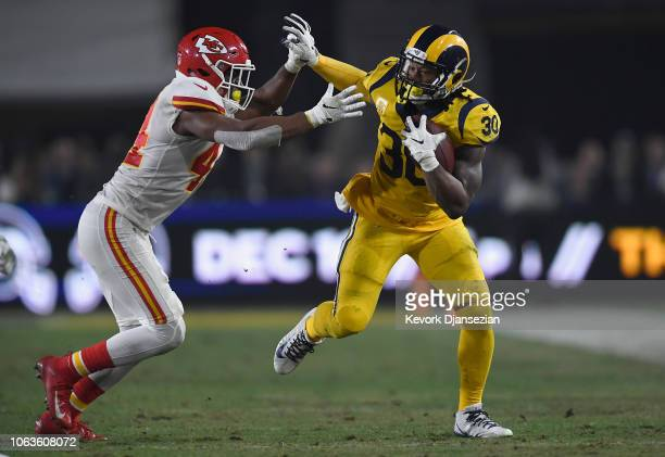 Todd Gurley of the Los Angeles Rams fends off Dorian O'Daniel of the Kansas City Chiefs during the third quarter of the game at Los Angeles Memorial...