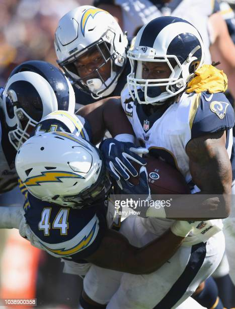 Todd Gurley of the Los Angeles Rams is tackled by Derwin James and Kyzir White of the Los Angeles Chargers during the third quarter of the game at...