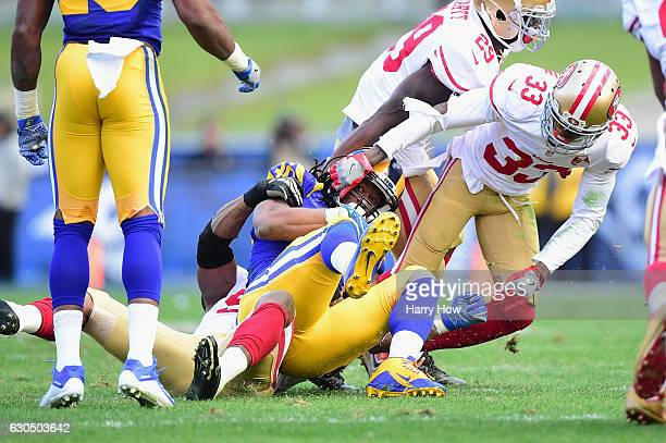 Todd Gurley of the Los Angeles Rams is tackled by Gerald Hodges and Rashard Robinson of the San Francisco 49ers during the first half of their game...