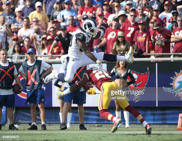 Todd Gurley of the Los Angeles Rams leaps over Bashaud Breeland of the Washington Redskins before scoring a touchdown during the third quarter at Los...