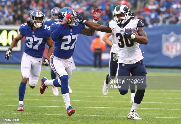 Todd Gurley of the Los Angeles Rams runs with the ball and chased by Darian Thompson of the New York Giants in the first quarter during their game at...