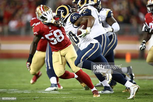 Todd Gurley of the Los Angeles Rams stiff arms Eli Harold of the San Francisco 49ers during their NFL game at Levi's Stadium on September 12 2016 in...