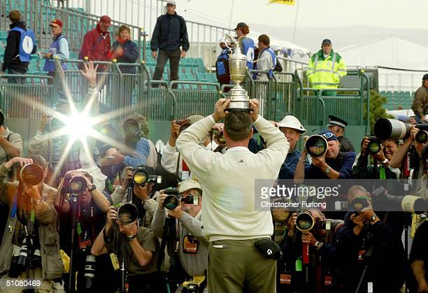 Todd Hamilton of USA poses with the claret jug on bis head in front of photographers after securing victory in the 133rd Open Championship after a...