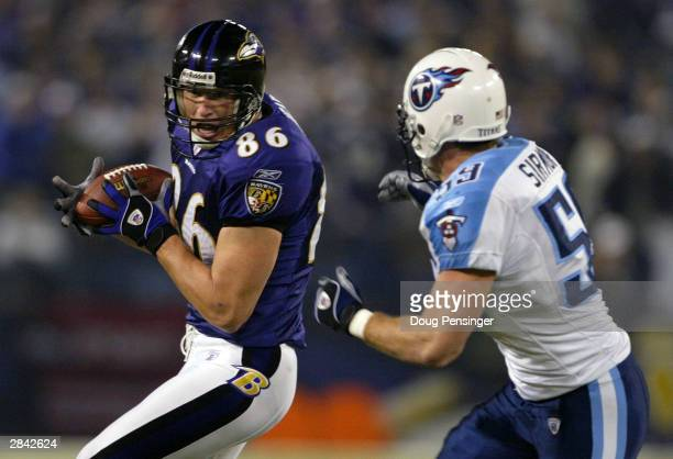 Todd Heap of the Baltimore Ravens hauls in a second quarter reception as Peter Simon of the Tennessee Titans closes in for the tackle during AFC...