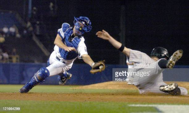 Todd Helton of the Colorado Rockies eludes tag of Los Angeles Dodgers catcher Brett Mayne to slide safety into home plate for the goahead run in the...