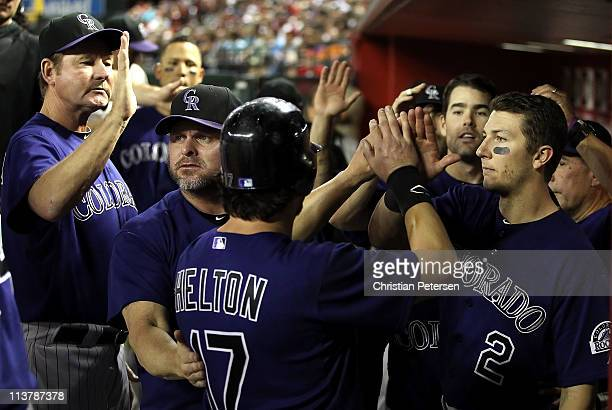 Todd Helton of the Colorado Rockies highfives teammates Carney Lansford Jason Giambi and Troy Tulowitzki after Helton scored a fourth inning run...