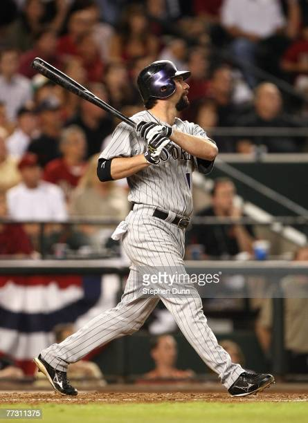 Todd Helton of the Colorado Rockies hits a sacrifice fly to score Willie Tavares in the top of the fifth inning against the Arizona Diamondbacks...