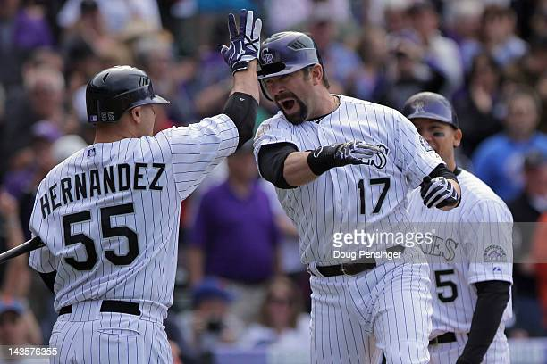 Todd Helton of the Colorado Rockies is welcomed home by Ramon Hernandez of the Colorado Rockies after his pinch hit grand slam home run off of relief...