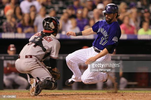 Todd Helton of the Colorado Rockies slides home past catcher Tuffy Gosewisch of the Arizona Diamondbacks to score on a sacrifice fly by Jordan...
