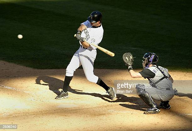 Todd Helton of the Colorado Rockies takes a swing but strikes out against catcher Rod Barajas and pitcher John Patterson of the Arizona Diamondbacks...
