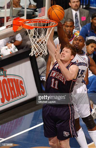 Todd MacCulloch of the New Jearsy Nets attempts to dunk the ball while being blocked from behind by Jahidi White of the Washington Wizards during a...
