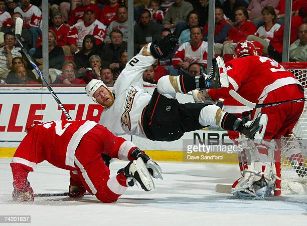 Todd Marchant of the Anaheim Ducks is knocked off his skates in front of the net by Chris Chelios of the Detroit Red Wings during the first period in...
