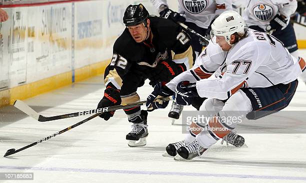 Todd Marchant of the Anaheim Ducks races for the puck against Tom Gilbert of the Edmonton Oilers on November 21 2010 at Honda Center in Anaheim...