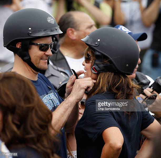 Todd Palin adjusts the strap of the motorcycle helmet of his wife former US Vice presidential candidate and Alaska Governor Sarah Palin before the...