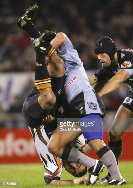 Todd Payten of the Tigers is tackled by Monty Betham of the Warriors during the round five NRL match between the Warriors and the Wests Tigers at...