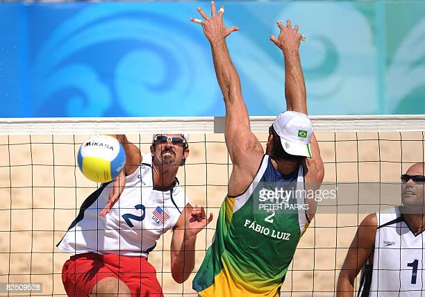 Todd Rogers of the US spikes a ball past Fabio Magalhaes of Brazil as his teammate Philip Dalhausser looks on in the final of the men's beach...