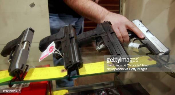 Todd Settergren of Setterarms gun shop, handles pistols inside his display case on Friday Jan. 13 in Walnut Creek, Ca. Settergren says California gun...