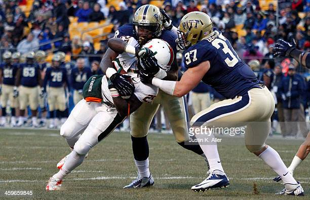 Todd Thomas of the Pittsburgh Panthers and David Durham of the Pittsburgh Panthers tackle Dallas Crawford of the Miami Hurricanes during the game on...